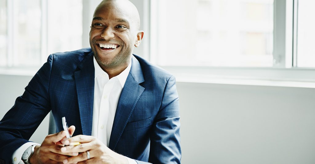 Smiling businessman in discussion at workstation in office