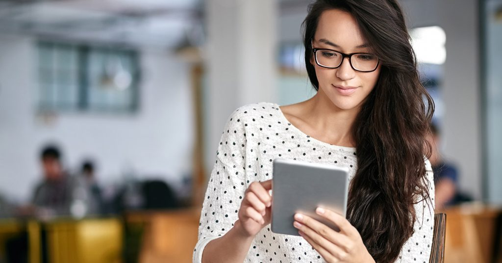 Shot of a young woman using a digital tablet while sitting in a modern office
