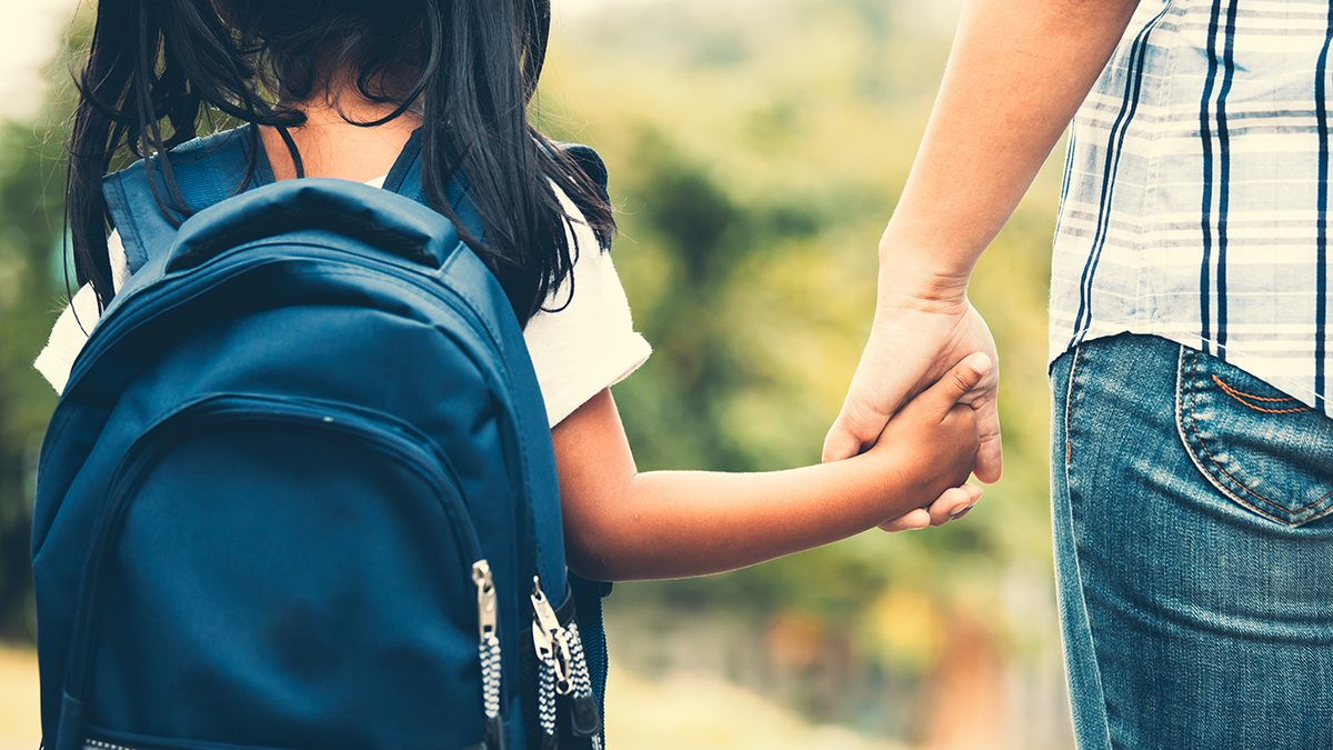 an image of a girl with a backpack holding hands w an adult