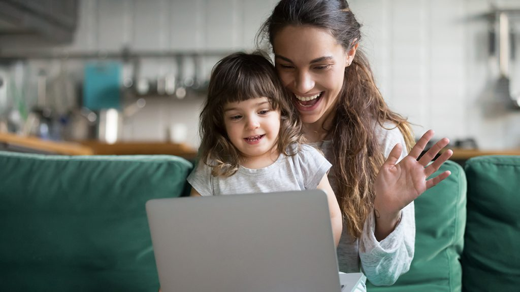 A mom and daughter sit in front of a laptop